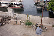 A local man locks his bicycle on the East Bank of the river Nile in Luxor, Nile Valley, Egypt.