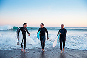 Father and sons happy and chatting after their surf, as they walk out of the water at St Ouen's Bay, Jersey, CI at sunset