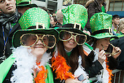 A trio of women in huge green hats watching the parade.