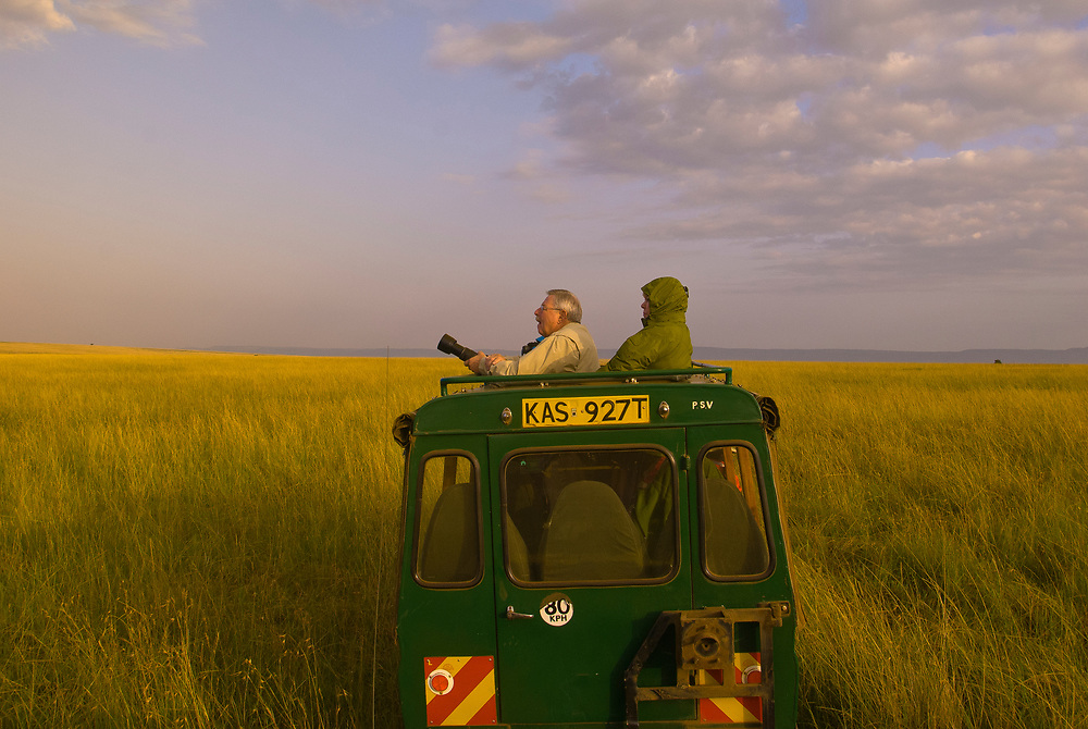 Tourists on safari observing wildlife from the open roof of a safari vehicle, Masai Mara National Reserve, Kenya