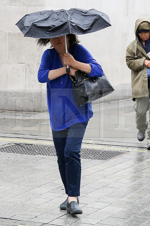 © Licensed to London News Pictures. 16/08/2019. London, UK. A woman shelters from the rain beneath an umbrella in Trafalgar Square. The Met Office has issued a severe weather alert for most of today, as almost a month's worth of rain is expected in many parts of the UK. Photo credit: Dinendra Haria/LNP