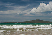The turqoise waters of the Hauraki Gulf of Auckland in New Zealand, splashing ashore on a hot summers day, with the volcanic island of Rangitoto in the background.