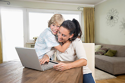 Boy hugging his mother while she online shopping on laptop, Bavaria, Germany