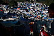 People walk in a camp for displaced people due to Jan.12 earthquake in downtown Port-au-Prince, Haiti, Feb. 2,  2010. (AP Photo/Rodrigo Abd)