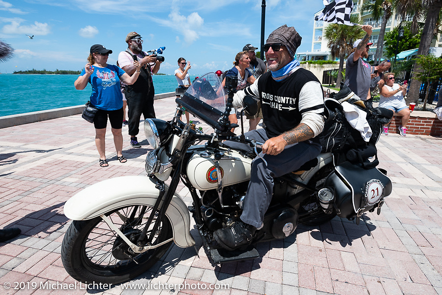 Tom Banks riding over the finish line on his 1936 Harley-Davidson VLH Flathead at the end of the Cross Country Chase motorcycle endurance run from Sault Sainte Marie, MI to Key West, FL. (for vintage bikes from 1930-1948). The Grand Finish in Key West's Mallory Square after the 110 mile Stage-10 ride from Miami to Key West, FL and after covering 2,368 miles of the Cross Country Chase. Sunday, September 15, 2019. Photography ©2019 Michael Lichter.