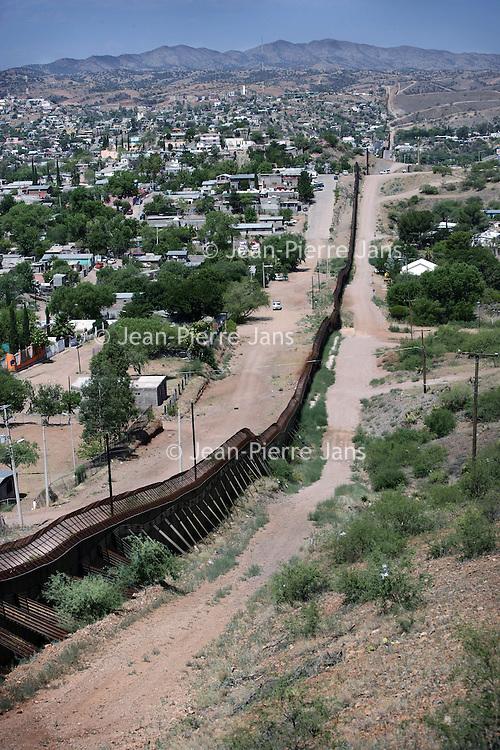 Verenigde Staten.Arizona 2005.<br /> Het Mexicaans Amerikaans grensplaatsje Nogales in het Zuiden van Arizona, gescheiden door een metalen muur, opgetrokken door de Amerikanen tegen de enorme stroom van illegalle vluchtelingen afkomstig uit Mexico en overwegend Latijns Amerikaanse landen.De grenspolitie moet toezicht zien op de stroom van illegalen die via Mexico de VS binnen tracht te komen.Grensplaats.Grens.Woestijn.Droogte.Gebergte.Vluchtelingen.Illegalen.Grensproblematiek.Illegale vluchteling.Mexicanen.Mexico.<br /> Archives 2005. Chase by police on illegal Mexicans who cross the border in Arizona.