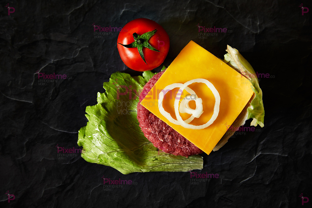 Hamburger iingredientes such as cheddar cheese, beef, onion, tomatoes, lettuce from top down in a dark black background