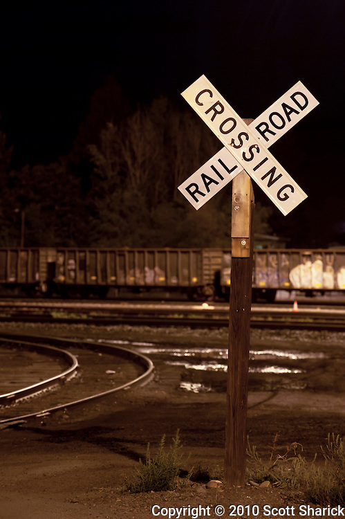A railroad crossing sign at night in a railyard. Missoula Photographer, Missoula Photographers, Montana Pictures, Montana Photos, Photos of Montana.