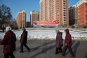 Residents walk past propaganda poster calling for people to unite and support Tonghua Steel in the Erdaojiang district in Tonghua, Jilin province, China, on Wednesday, Jan. 6, 2016. The citys once-vaunted state-run steel mills have slipped inexorably into decline, weighed down by slumping global markets, a changing economy, and the burden of costs and responsibilities to the people of the town they fostered. Previous attempts to privatise the enterprise have met with stiff resistance, one such attempt resulted the mob lynching and death of a private businessman who wanted to invest and streamline the operation.