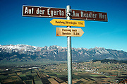A mountain top footpath signpost above a Liechtenstein valley with the town of Nendeln below. The tiny landlocked alpine principality has 400 kilometers (250 miles) of well prepared and marked hiking paths high up in the mountains and down in the valley. Typically, a one-hour route starts from Nendeln post office and goes to Oberstädtle on forest paths then to Nendler on narrow mountain path, to Brunnenbühl through forest to Planken.