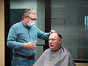 15 MAY 2020 - DES MOINES, IOWA: BRUCE FULTON, a barber at Ferg's Barbershop in downtown Des Moines, cuts a clients' hair. The barbershop opened Friday for the first time in two months and by midday was completely booked through next week. The Governor of Iowa allowed most businesses in Iowa to reopen today, including restaurants, barbershops, coffee shops and malls. Restaurants are supposed to be working at 50% of normal capacity and barbershops are urged to take reservations and not allow customers to wait in the shop.  Movie theaters, bars, museums, zoos, and casinons are still closed. On Friday, 15 May, Iowa reported 14,049 cases of COVID-19 and 336 deaths from disease since the start of the pandemic. Iowa's total number of infections continue to rise and several communities in Iowa have emerged as national hotspots for the spread of Coronavirus (SARS-CoV-2).        PHOTO BY JACK KURTZ