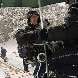 A large umbrella is placed over the camera while the tracks of the traveling are swept of snow.