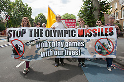 © licensed to London News Pictures. London, UK 28/07/2012. Protester posing with banners against the defence precautions as anti-Olympics protesters marching from Mile End Park to Victoria Park in order to protest against the greed of the Olympic sponsors. Photo credit: Tolga Akmen/LNP