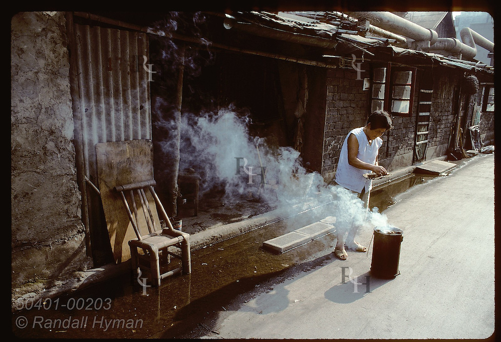 Woman tends small cooking stove outside her humble bamboo shack in industrial area of Shanghai. China