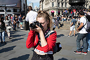 Young woman taking pictures on her Canon SLR camera at Piccadilly in London, United Kingdom. Digital photography has made the art form incredibly accessible.