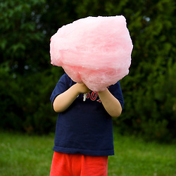 A young boy (age 3) enjoys cotton candy at the Quechee Balloon Festival, Quechee, Vermont.
