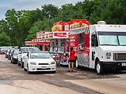 "26 JUNE 2020 - DES MOINES, IOWA: People in their cars wait in line for their lunch at Fair Food Friday in Des Moines. The 2020 Iowa State Fair, like many state fairs in the Midwest, has been cancelled this year because of the COVID-19 (Coronavirus) pandemic. The cancellation of the fair left many small vendors stranded with no income. Some of the fair food vendors in Iowa started ""Fair Food Fridays"" on a property a few miles south of the State Fairgrounds. People drive up and don't leave their cars while vendors bring them the usual midway fare; corndogs, fried tenderloin sandwiches, turkey legs, deep fried Oreos, lemonaide and smoothies. Fair Food Friday has been very successful. The vendors serve 450-500 people per Friday and during the lunch rush people wait in line in their cars 30 - 45 minutes to place an order.      PHOTO BY JACK KURTZ"