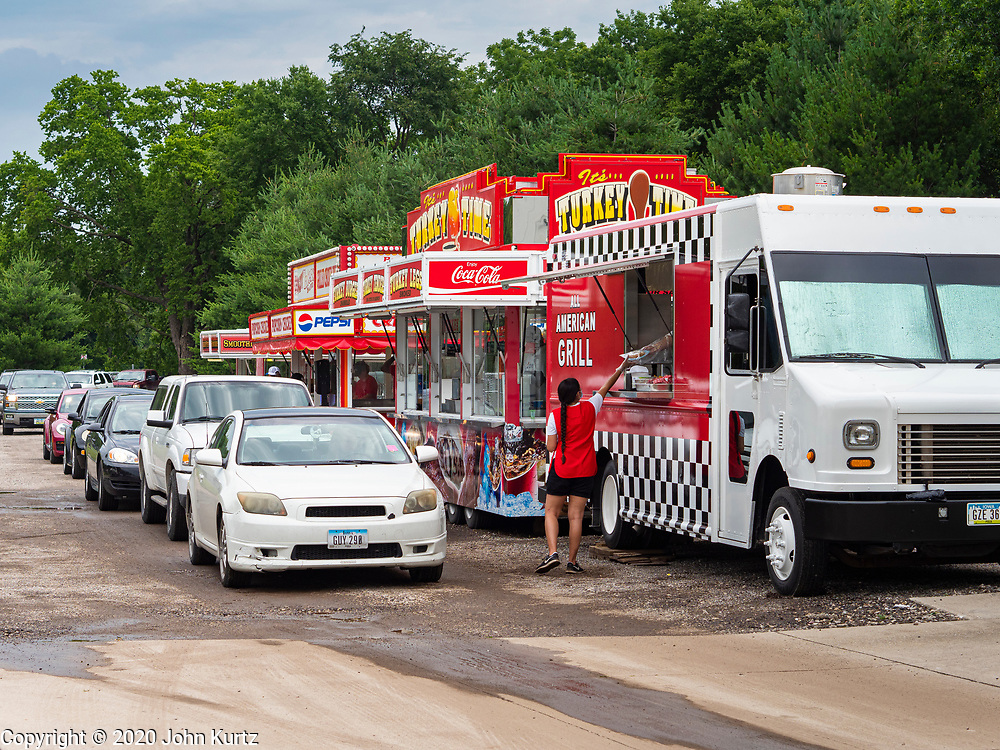 """26 JUNE 2020 - DES MOINES, IOWA: People in their cars wait in line for their lunch at Fair Food Friday in Des Moines. The 2020 Iowa State Fair, like many state fairs in the Midwest, has been cancelled this year because of the COVID-19 (Coronavirus) pandemic. The cancellation of the fair left many small vendors stranded with no income. Some of the fair food vendors in Iowa started """"Fair Food Fridays"""" on a property a few miles south of the State Fairgrounds. People drive up and don't leave their cars while vendors bring them the usual midway fare; corndogs, fried tenderloin sandwiches, turkey legs, deep fried Oreos, lemonaide and smoothies. Fair Food Friday has been very successful. The vendors serve 450-500 people per Friday and during the lunch rush people wait in line in their cars 30 - 45 minutes to place an order.      PHOTO BY JACK KURTZ"""