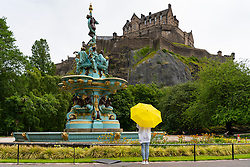 Edinburgh, Scotland, UK. 23 June, 2020. A woman with yellow umbrella used as a parasol admires the  Ross Fountain and Edinburgh Castle from West Princes Street Gardens during sunny warm afternoon in Edinburgh. Iain Masterton/Alamy Live News