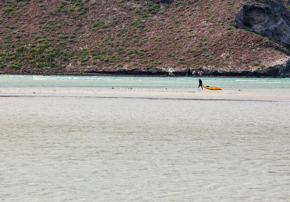 A man dragging his kayak  to deeper water at Balandra Beach, BCS Mexico.