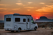 Pleasure-Way RV at sunrise near Little Wild Horse Canyon in San Rafael Swell Recreation Area, Utah, USA. Hike a classic loop from Little Wild Horse Canyon to Bell Canyon. This great walk (an 8.6-mile circuit with 900 feet gain) is a short drive on a paved road from Goblin Valley State Park. The hike via fascinating narrow slot canyons and open mesas requires some scrambling over rocks, possibly through shallow water holes (which were dry for us on Sept 20, 2020 but wet in April 2006). Thanks to the greatest legislative victory in the history of SUWA (Southern Utah Wilderness Alliance), in 2019, Congress passed the Emery County Public Land Management Act, which declared 663,000 acres of wilderness, including Little Wild Horse Canyon Wilderness, in San Rafael Swell Recreation Area, Utah, USA. The Navajo and Wingate sandstone of the San Rafael Reef was uplifted fifty million years ago into a striking bluff which now runs from Price to Hanksville, bisected by Interstate 70 at a breach fifteen miles west of the town of Green River.