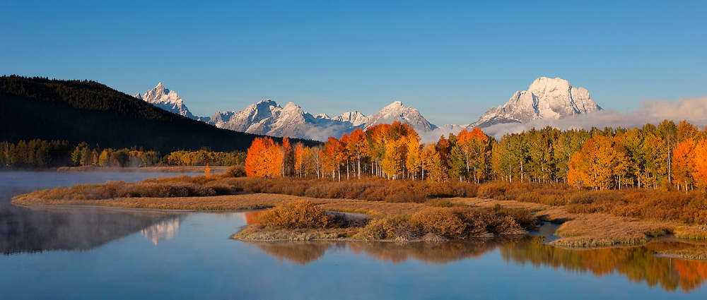 The mountains of Grand Teton National Park, Wyoming, tower above Oxbow Bend, which is lined with autumn color, on a foggy morning. Among the major mountains visible (from left to right): Grand Teton, Rockchuck Peak, Mount Woodring, and Mount Moran.