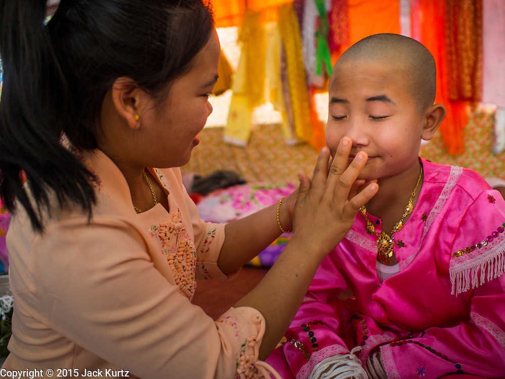 """05 APRIL 2015 - CHIANG MAI, CHIANG MAI, THAILAND: Tai Yai women get the boys in their family ready to be ordained as Buddhist novices during the second day of the three day long Poi Song Long Festival in Chiang Mai. The Poi Sang Long Festival (also called Poy Sang Long) is an ordination ceremony for Tai (also and commonly called Shan, though they prefer Tai) boys in the Shan State of Myanmar (Burma) and in Shan communities in western Thailand. Most Tai boys go into the monastery as novice monks at some point between the ages of seven and fourteen. This year seven boys were ordained at the Poi Sang Long ceremony at Wat Pa Pao in Chiang Mai. Poy Song Long is Tai (Shan) for """"Festival of the Jewel (or Crystal) Sons.    PHOTO BY JACK KURTZ"""