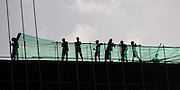 Men working on construction fence on top of building, Nyaung Shwe