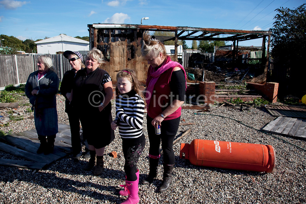 McCarthy sisters and family stand defiantly beside a burned out building at Dale Farm site prior to eviction. Riot police and bailiffs were present on 20th October 2011, as the site was cleared of the last protesters chained to barricades. Dale Farm is part of a Romany Gypsy and Irish Traveller site in Crays Hill, Essex, UK. <br /> <br /> Senior resident Kathleen McCarthy said she now wished to leave, once obstacles are removed, and the majority of residents are expected to join her. Most plan to relocate to Oak Road, on the neighbouring legal site.<br /> <br /> Dale Farm housed over 1,000 people, the largest Traveller concentration in the UK. The whole of the site is owned by residents and is located within the Green Belt. It is in two parts: in one, residents constructed buildings with planning permission to do so; in the other, residents were refused planning permission due to the green belt policy, and built on the site anyway.