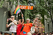 Spectators at the iconic corner of Gay Street and Christopher Street watch the 2011 Pride Parade in New York's West Village.