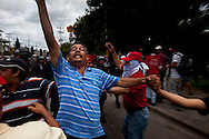 5 July 2009 - Tegucigalpa, Honduras - Supporters of ousted Honduras' President Manuel Zelaya  block other protestors from provoking police during a protest march outside the airport in Tegucigalpa. President Zelaya was unable to land today, but pledged to return in the coming days. His supporters have been marching in the capital's streets since he was ousted last Sunday, but the protests have increased dramatically in the last few days.