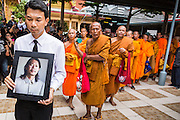 28 APRIL 2014 - BANGKOK, THAILAND: A mourner carries a photo of Kamol Duangphasuk, 45, in front of a line of Buddhist monks during Kamol's funeral in Bangkok. Kamol was a popular poet who wrote under the pen name Mai Nueng Kor Kunthee. Kamol had been writing since the 1980s and was an outspoken critic of the 2006 coup that deposed Thaksin Shinawatra. After the 2010 military crackdown against the Red Shirts he went into temporary self imposed exile fearing for his safety. After he returned to Thailand he organized weekly protests against Thailand's Lese Majeste laws, which he said were being used to stifle dissent. Kamol was shot and murdered on April 23. The assailants are still at large but the murder is thought to be political.     PHOTO BY JACK KURTZ
