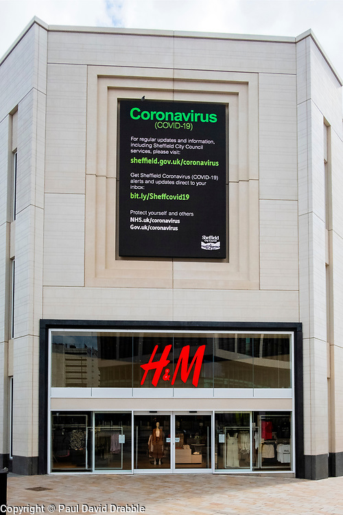 """Sheffield Friday 3 April 2020 <br /> Coronavirus Covid-19 """"Protect Yourself And Others"""" advice sign on an electric advertising hoarding above the entrance to H&M Fashion retailer at the top of The Moore Sheffield<br /> <br /> 3 April 2020<br /> <br /> www.pauldaviddrabble.co.uk<br /> All Images Copyright Paul David Drabble - <br /> All rights Reserved - <br /> Moral Rights Asserted -"""