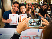 "14 FEBRUARY 2017 - BANGKOK, THAILAND:  A couple has their wedding photo taken with their iPhone in the Bang Rak district in Bangkok. Bang Rak is a popular neighborhood for weddings in Bangkok because it translates as ""Village of Love."" (Bang translates as village, Rak translates as love.) Hundreds of couples get married in the district on Valentine's Day, which, despite its Catholic origins, is widely celebrated in Thailand.     PHOTO BY JACK KURTZ"