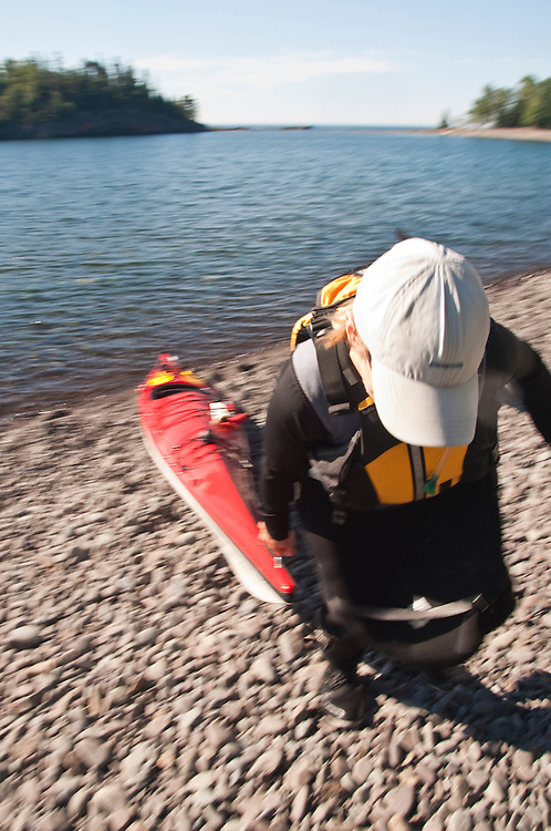 Sea kayaker pulls a kayak higher up a beach.