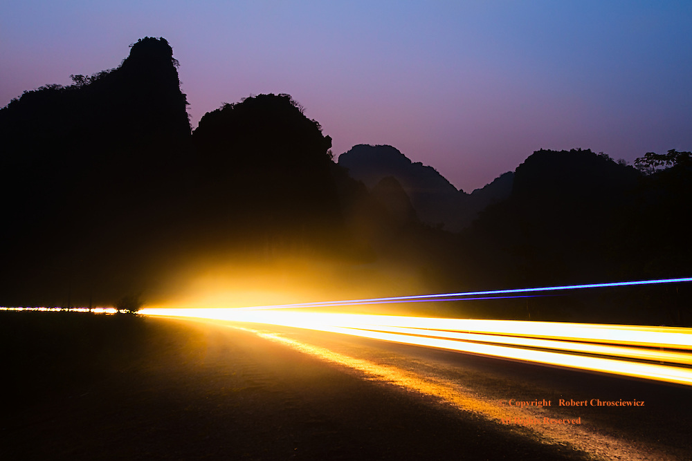 Mornings' Light: Jagged limestone hills form the backdrop for this timed photograph of the long streaking automobile lights in an early morning sunrise, Tha Khek Laos.