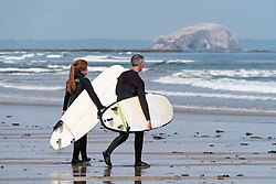 Two  surfers carry surfboards to sea at Belhaven Beach, East Lothian, Scotland, United Kingdom