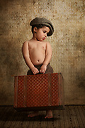 an old style image of a toddler with a packed suitcase ready to leave home