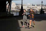 Lunchtime joggers run past through winter light on the riverfront walkway. The South Bank is a significant arts and entertainment district, and home to an endless list of activities for Londoners, visitors and tourists alike.