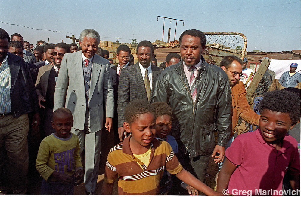 Joao Silva (right) moves past Tokyo Sexwale as Nelson Mandela visits the shanty town of Phola Park in Thokoza, east of Johannesburg at the height of the violence in 1990. (Photo Greg Marinovich)
