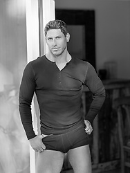 good looking man pulling down his briefs while standing in a doorway at home