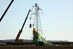 ©Licensed to London News Pictures. 26/03/2012.Bozeat, Northamptonshire. Workmen help remove hotair balloon. A hot-air balloon crashed into power lines in Northamptonshire, trapping a woman and two men 15m in the air.<br />