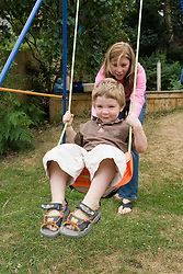 Nanny and little boy playing on the swing in the garden,