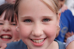 Portrait of primary school girl standing in playground smiling,
