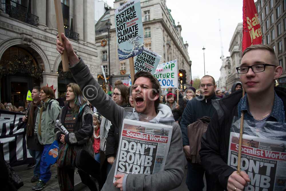 London, UK. Sunday 29th November 2015. Peoples March for Climate Justice and Jobs demonstration. Demonstrators gathered in their tens of thousands to protest against all kinds of environmental issues such as fracking, clean air, and alternative energies, prior to Major climate change talks. One demonstrator with a copy of Socialist Worker calling not to bomb Syria.