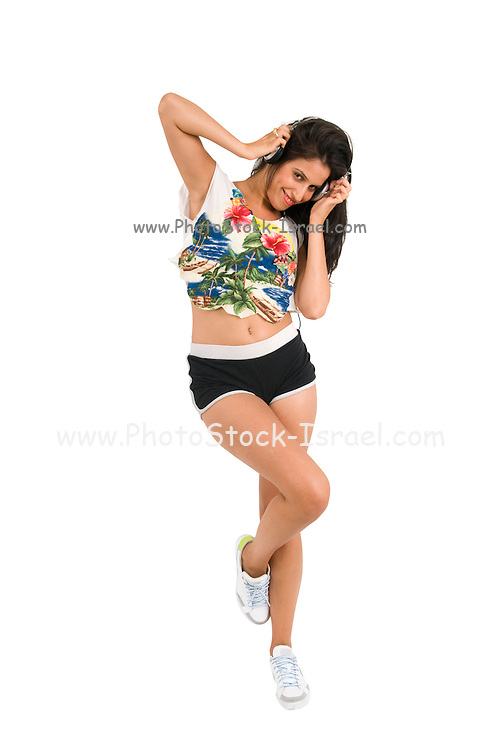 Young woman in sportswear with headphones dances on white background