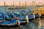 Gondolas in the early morning sun - Vnice Italy. . The gondola ( góndoła ) is a traditional, flat-bottomed Venetian rowing boat, well suited to the conditions of the Venetian lagoon.  gondolas are typically propelled by a gondolier, who uses a rowing oar, which is not fastened to the hull, in a sculling manner and also acts as the rudder. The oar of the  gondola rests in an elaborately carved wooden rest (forcola) shaped to project from the side of the craft so as to allow the slight drag of each return stroke to pull the bow back to its forward course. For centuries, the gondola was a major means of transportation and the most common watercraft within Venice. .<br /> <br /> Visit our ITALY HISTORIC PLACES PHOTO COLLECTION for more   photos of Italy to download or buy as prints https://funkystock.photoshelter.com/gallery-collection/2b-Pictures-Images-of-Italy-Photos-of-Italian-Historic-Landmark-Sites/C0000qxA2zGFjd_k