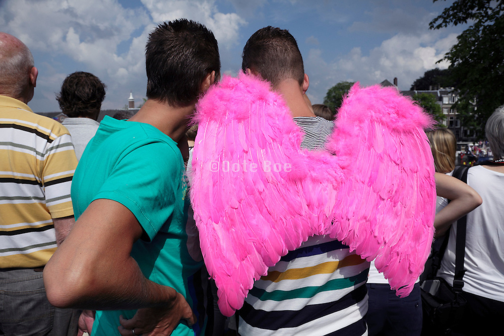 young adults of which one wears pink angel wings