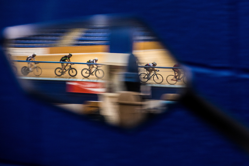 A group of cyclists practice through a reflection of a motorbike's mirror at the Velo Sports Center, a Velodrome in Carson, California on November 3, 2016.