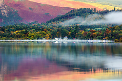 © Licensed to London News Pictures. 15/10/2018. Keswick UK. The mountains that surround Derwentwater reflect into the calm water just after sunrise this morning on a cold start to the day in Keswick, Cumbria. Photo credit: Andrew McCaren/LNP